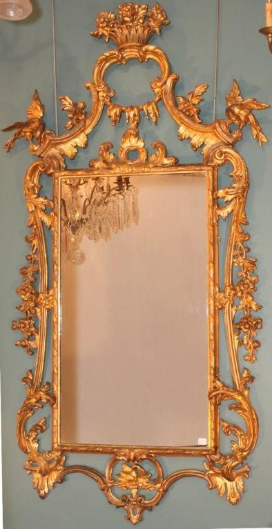 Carved and gilded wood mirror frame featuring ho-ho birds in open scrollwork flanking pediment of floral urn.
