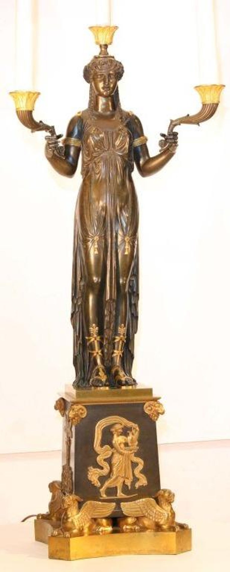 Crisply modelled as a standing godess, supporting ebonised and gilt arms, her slender body clad in a clinging toga with gilt tassels , arm bands, and sandals. She stands on an elaborate tapering square base base applied with gilt mounts and raised