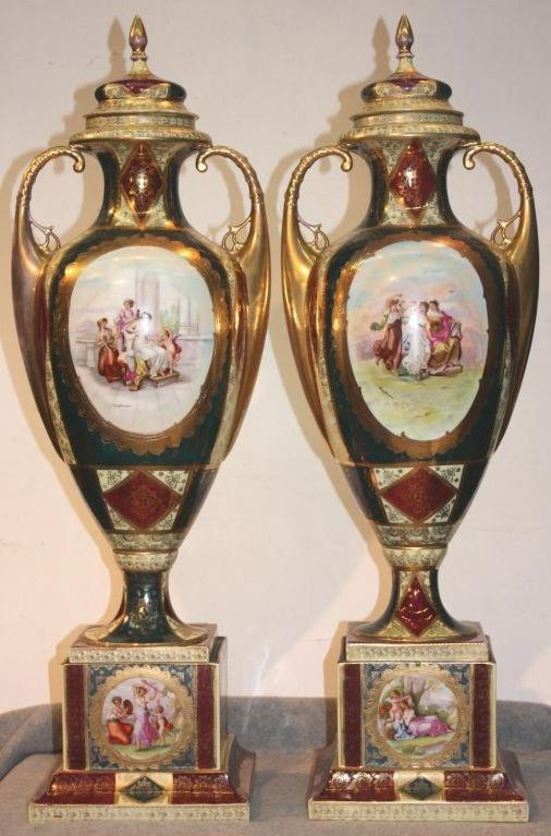 Pair of Royal Vienna parcel-gilt two handled covered vases on square stepped plinths, cream glaze and teal and red overglaze enamels, with classical scenes in gilt cartouches, copied after the artist, Angelica Kauffmann. Elaborate lacy gilt scrolls
