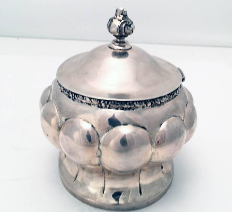Austrian Secessionist silver sugar or etrog box of lobed oval outline, with waisted body and with domed oval hinged cover, applied with an urn shaped finial, with gilt interior.