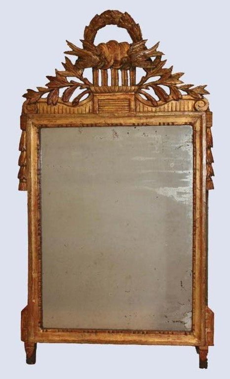Louis XVI period carved and giltwood wall mirror, the pediment of doves of peace fronting a laurel wreath; the sides with trailing bellflowers.