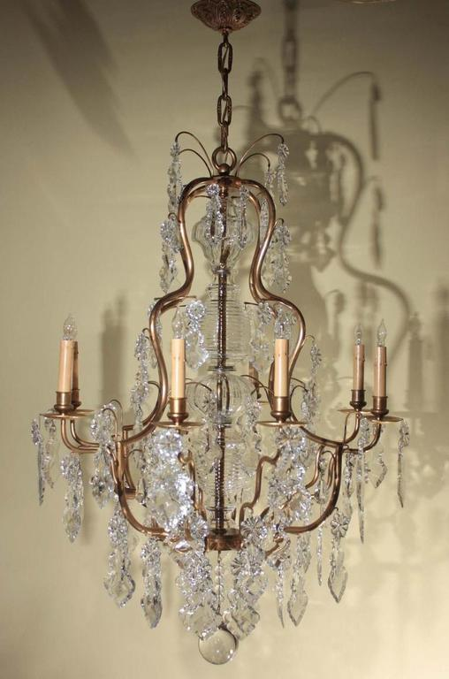 Louis XV style eight-light chandelier, the shaped  cage centered by crystal shaft , heavily laden with French pendeloque crystals and terminating in ball finial.