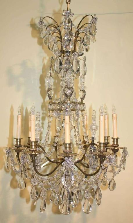 Louis XVI style gilt bronze and crystal twelve light chandelier by Maison Baguès, with  nine scrolling arms swagged with crystal garlands. and three downswept lights.  The central shaftis  clad in  crystal surmounted by a corona of half moon pear