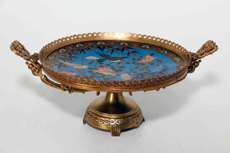 An antique French centerpiece the gilt bronze body with turned stem, raised feet and with pierced rim and handles. Mounted in this centerpiece is a Japanese cloisonné plate, worked with birds in flowering prunus blossoms.  This centerpiece, was