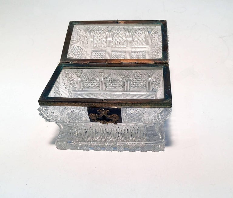 Unlike most similar boxes this one is of sarcophagus form, more costly to produce and more difficult to cut. This sort of quality is very frequently by Baccarat. The high light and clear metal of the glass would also support that view, as would the