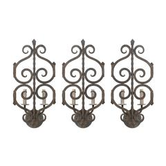 A Set of Three French Two-Light Forged Iron Sconces Featuring Scroll Decor