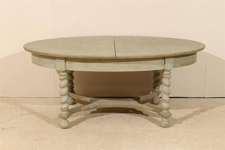 A Swedish Baroque style mid-20th century oval table. This painted wood table features barley twist legs and a nicely shaped cross stretcher. The table is raised on ball feet. The simplicity of the top is nicely balanced by the carving of the legs