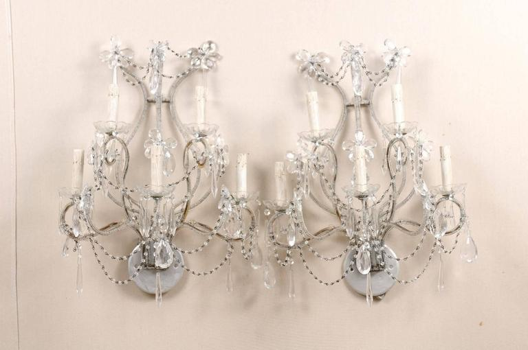 A pair of Italian crystal sconces. This pair of Italian crystal sconces from the mid-20th century features five lights with glass bobèches divided on two levels. The metal armature and backplate have been painted grey. Delicate beading, strands,