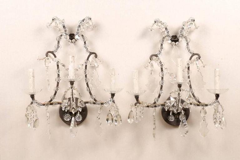 A pair of crystal three-light sconces. This pair of Italian vintage sconces is made of a scrolled armature decorated with small size crystal flowers and glass bobèches. The sconces are also decorated with various faceted crystals. The back plate