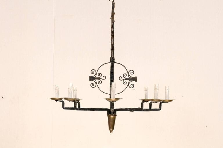 An Italian vintage circular eight-light wrought iron chandelier. This mid-20th century Italian iron chandelier features a central post with globe flanked with volutes on each side, leading to a twisted beam with a diamond shaped post top and hook.