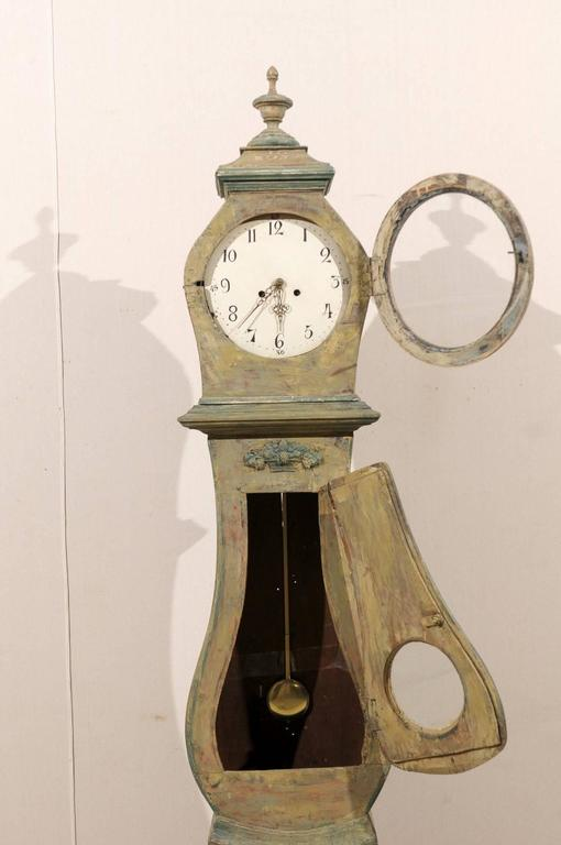 A Swedish 19th century clock. This painted wood clock features a nicely carved crest with an urn in its center. The neck is decorated with an exquisite fruit basket motif in its center. This clock retains it's original metal face, hands and