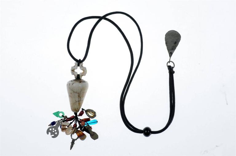A custom-made necklace by Famous Moroccan Jeweler Chez Faouzi of Marrakech. Necklace features a conus shell along with a charming collection of Moroccan beads, shells and artifacts. Black cord necklace is adjustable to a maximum of 38.