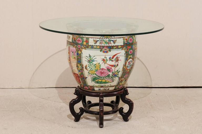 A Chinese Famille rose base and glass top table. This round-shaped Chinese table features a glass top over a large Famille rose porcelain vase. There are beautiful depictions of birds and flowers about the outside of the base with koi and aquatic