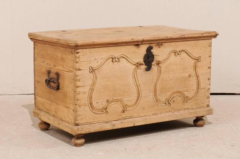 A Swedish 19th century wood coffer. This Swedish trunk from the 19th century features carved pine wood featuring an oval design at its top and two carved patterns on the front, reminiscent of a pair of shields. This pine chest has a natural wood