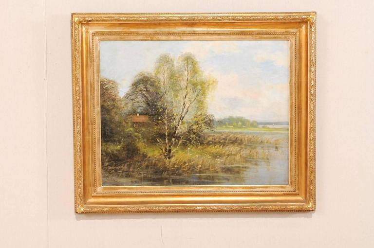 A Swedish landscape oil painting in frame. This is a lovely painting depicts a homestead and surrounding landscape by the water. This painting is within a gold wood carved frame. Signed