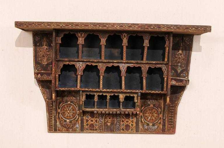 A mid-20th century Moroccan spice rack. This vintage Moroccan handmade and painted wood spice rack features a three terraced shelf design, and is elaborating adorn in various patterns, decorations, and colors typical of Moroccan art. Though this