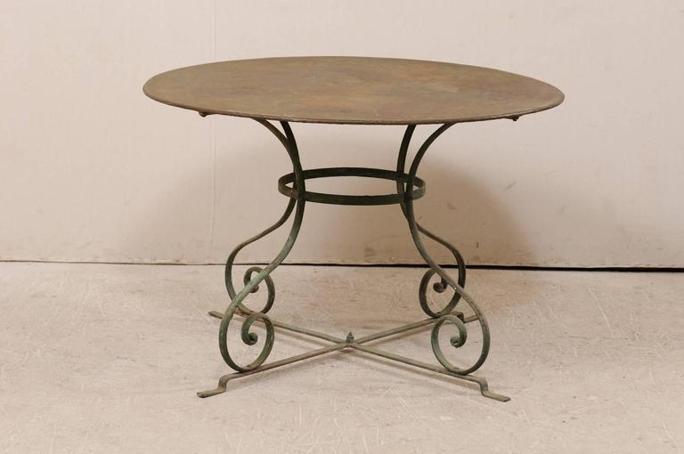 A French mid-20th century patio dining table. This round shaped metal patio table has a wonderfully aged patina and features a round top over four scrolling legs. Each of the four legs are connected to a circular center and bottom cross bar for