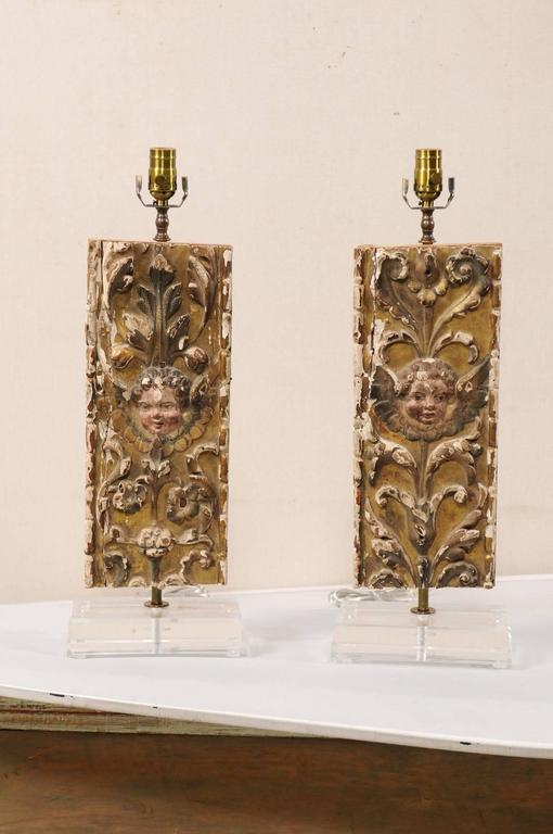 A pair of custom 18th century Italian fragment table lamps. This pair of Italian gilt and gesso over wood lamps feature a decor of rinceaux and acanthus leaves with the face of a putti at center. These fragments are raised on custom Lucite bases.