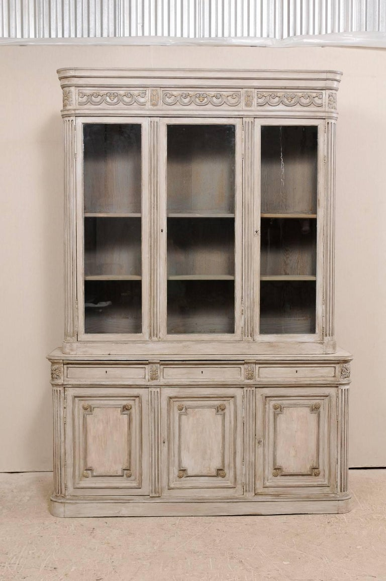 A 19th century French tall wood and glass cabinet. This tall French antique  cabinet has - French 19th Century Neutral Painted Wood And Glass Tall Cabinet With