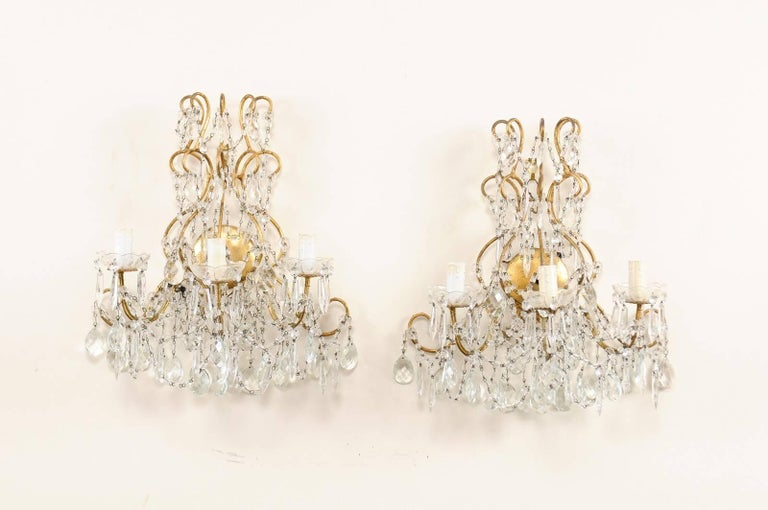 A pair of Italian vintage three-light crystal sconces. This pair of Italian crystal sconces each feature a variety of faceted crystals ornately decorating the scrolled and gilded metal armature and arms. Strands of crystals are heavily draped