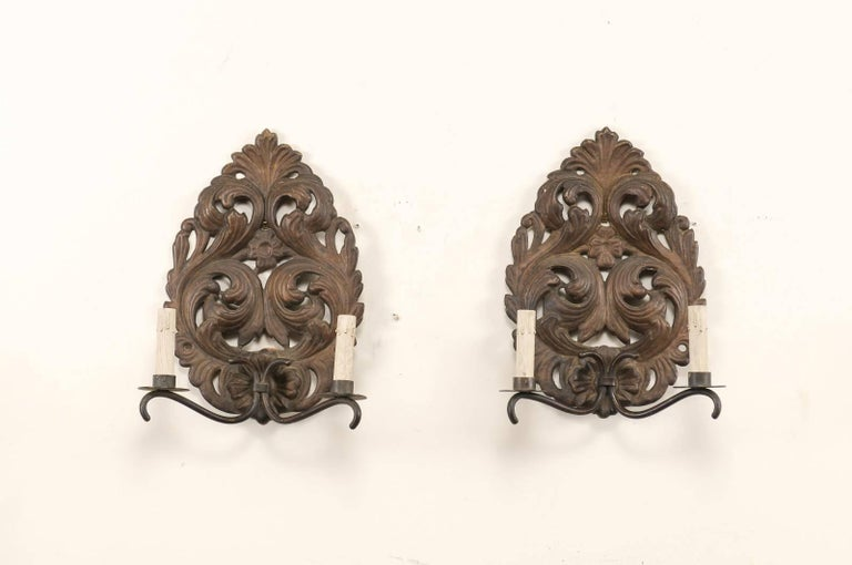 A pair of Italian two-light unwired sconces from the mid-20th century. This pair of Italian sconces each feature tole, raindrop-shaped backplates which are ornately decorated in a scrolling acanthus leaf motif. There are two gently curved metal arms