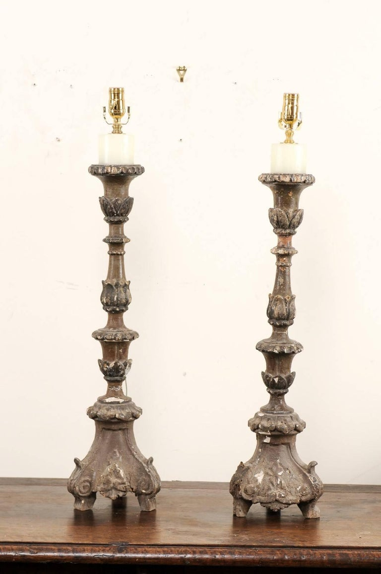 A pair of Italian 18th century carved wood altar sticks made into table lamps. This pair of Italian table lamps has been fashioned from antique altar sticks with gesso and old paint over carved wood. They feature beautifully carved bodies with leaf