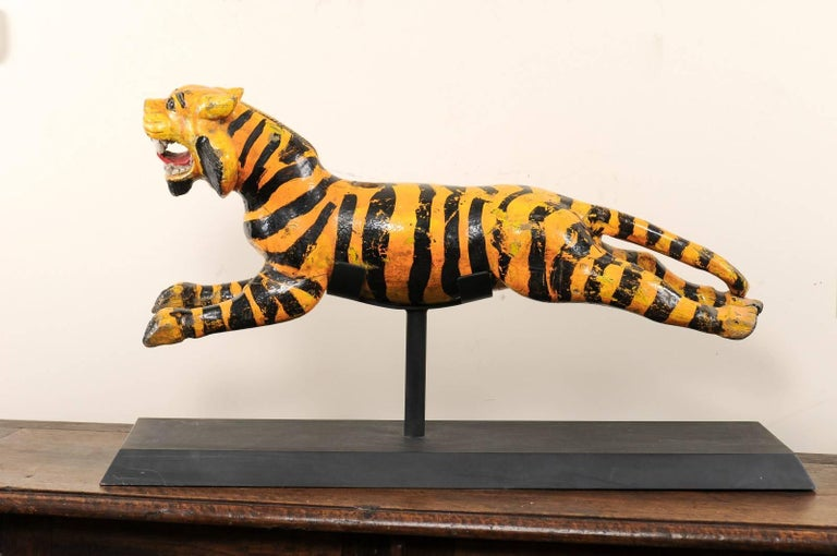 A vintage Burmese carousel tiger. This whimsical tiger was originally part of a merry-go-round in Burma during the 20th century. The tiger has the appearance of being in mid-run, open mouthed and bearing its teeth. It is made of painted wood, the