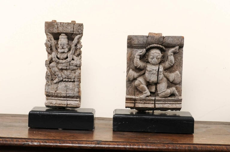 A pair of 19th century Hindu temple fragments. This pair of antique fragments were elements of a section of hand-carved wood frieze, within a temple in India. They have each been mounted on a custom-made, rectangular-shaped, and black painted wood