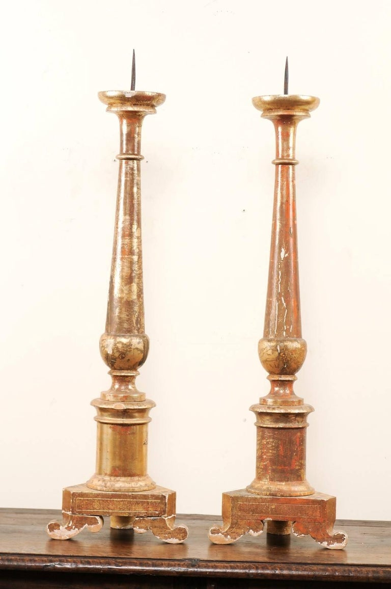 Pair of Italian, 19th century gilded altar sticks. This pair of antique Italian altar sticks are more than 3 ft tall and each feature a beautifully turned central column which has been lifted up on a triangular-shaped base and three curved bracket