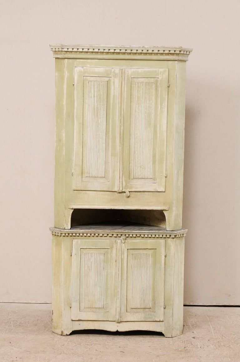 A Swedish late 18th century period Gustavian painted wood corner cabinet. This Swedish Gustavian corner cabinet features reeded doors, dentil molding just below the upper cornice and mid section, and a scalloped accolade style carved skirt. This