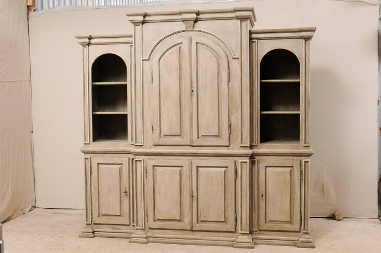 A large sized vintage Brazilian painted wood cabinet. This impressive display cabinet features a heavily molded cornice and base, and nicely arched tops framing the upper display cabinets. This cabinet has a stepped out and larger center section of