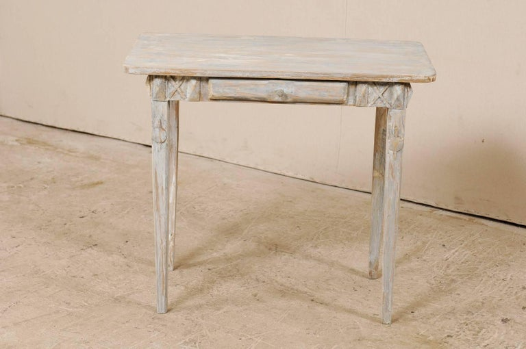 A Swedish period Gustavian, 19th century painted wood side table. This antique Swedish small sized table features nice clean lines, a rectangular-shaped top, and single drawer. The drawer is flanked with x-style carvings and has a carved wood pull