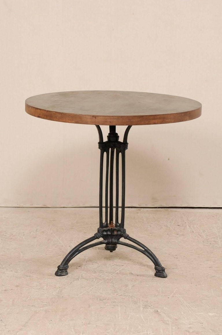 A French iron bistro table. This French bistro table consists of a early 20th century iron base with a contemporary top. This Industrial style bistro table is round-shaped and features a central black iron centered column base with tri-pod feet and