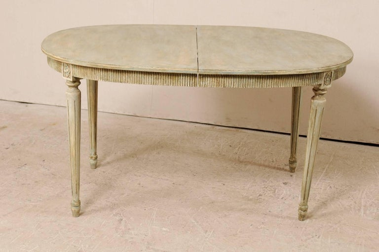 A vintage Swedish Gustavian Style painted wood table. This Swedish table features an oval-shaped top, and a reeded apron with carved rosette accent pieces above which are above each of its four rounds, fluted and gently tapered legs. The coloring is