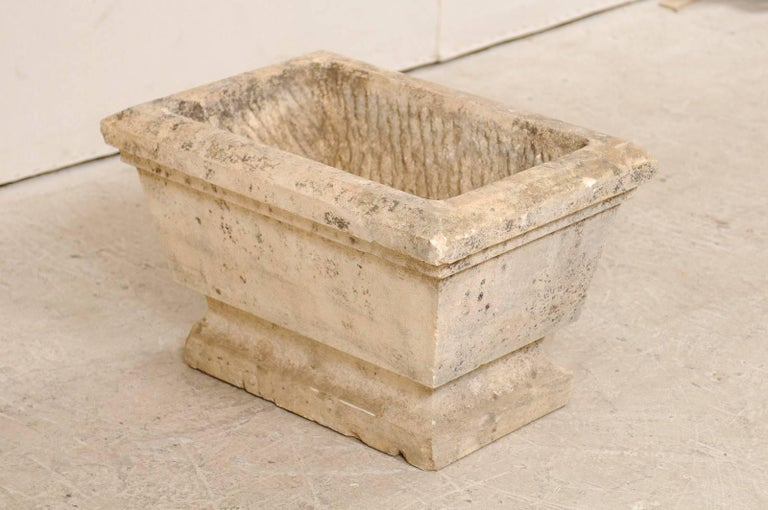 A European stone planter from the early 20th century. This antique, hand-carved stone planter has an overall rectangular-shape which tapers slightly towards the bottom. Just below the main body, the stone is carved concavely, and then back out into