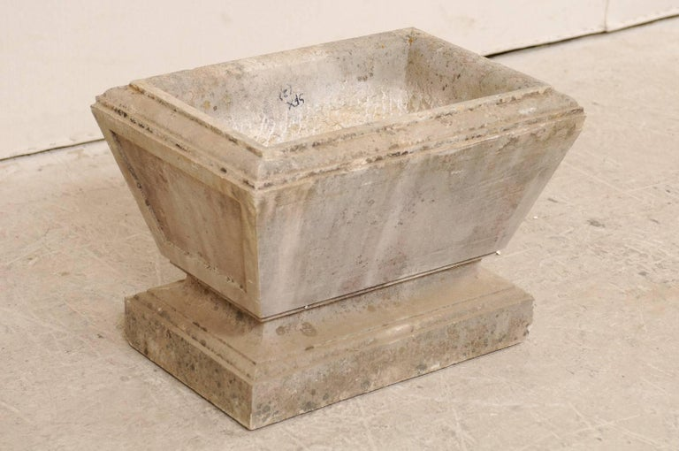 A European stone planter from the early 20th century. This antique, hand-carved stone planter has an overall rectangular-shape, with recessed panel designed sides, which tapers slightly towards the bottom. Just below the main body, the stone is
