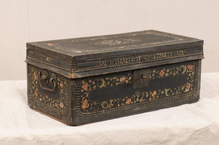 A 19th century Chinese camphor wood chest. This antique Chinese camphor wood trunk features a beautifully hand-painted flower motif on it's leather covered exterior, adorn with a decorative trimming of nail heads, and brass bound edges. The chest