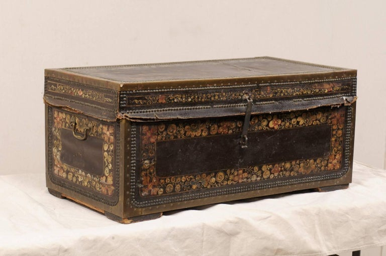 A 19th century Chinese camphor wood trunk. This antique Chinese camphor wood chest features a beautifully hand-painted flower motif on it's leather covered exterior, adorn with a decorative trimming of nail heads, and brass bound edges. The chest