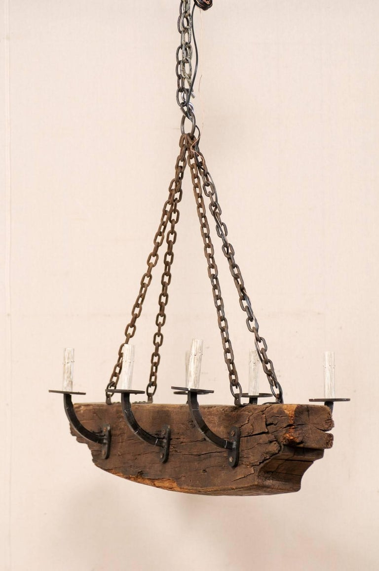 A vintage French six-light rustic beam and metal arms chandelier. This French mid-20th century chandelier has a central wooden beam with six forged iron arms, three at each opposing side. The six arms are simply designed, gently rising up and away