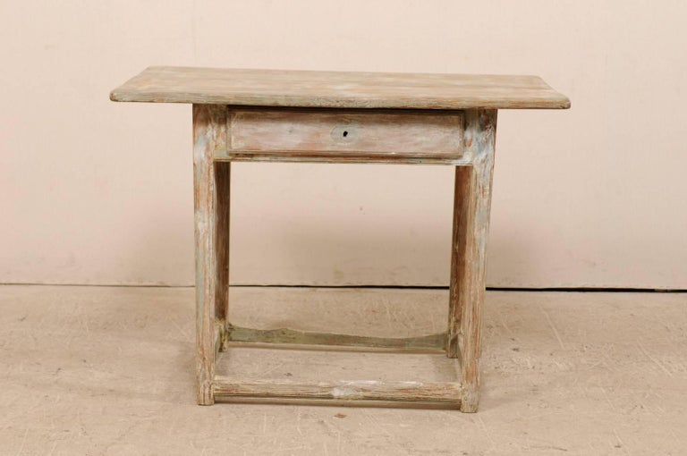 A period Gustavian Swedish fir wood side table. This Swedish table from the early 19th century features, simple, clean lines, an over-hung and rectangular-shaped top, and single drawer. This table is raised on four squared legs, and supported with