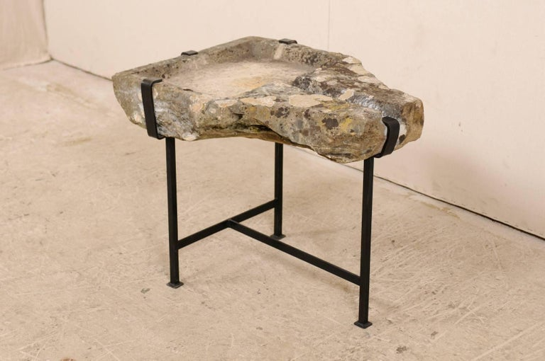 An early 19th century French stone trough coffee table on custom base. This unique coffee table features a top made from a French stone trough which dates back to the early 19th century (or possibly older). The stone trough top is supported by a