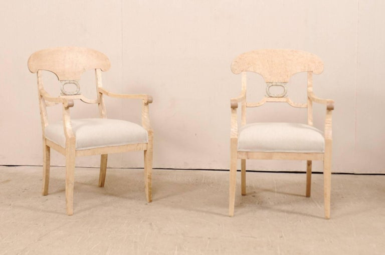 A pair of Swedish Biedermeier or Karl Johan arm chairs from the late 1800s. These 19th century Swedish bleached curly birch arm chairs feature classically curved