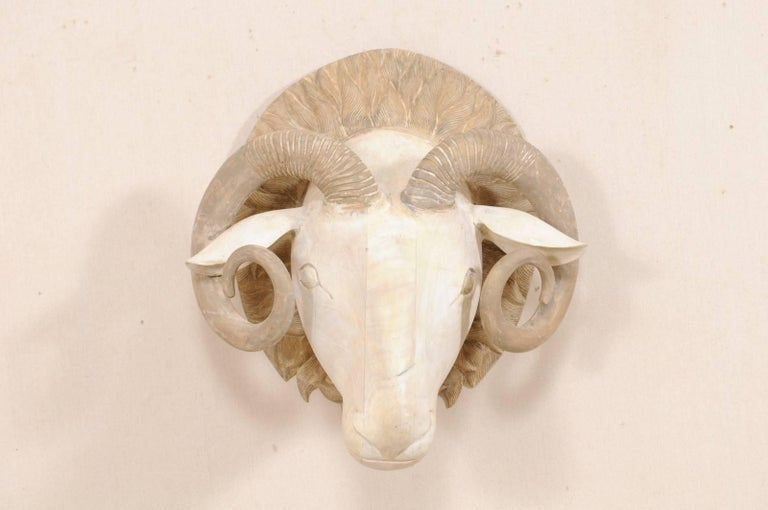 A carved wooden ram's head. This hand-carved ram's head features a forward facing three-dimensional ram with beautifully curled and textured horns, mounted onto a rounded wooden back plate which has been nicely carved and decorated. This ram has