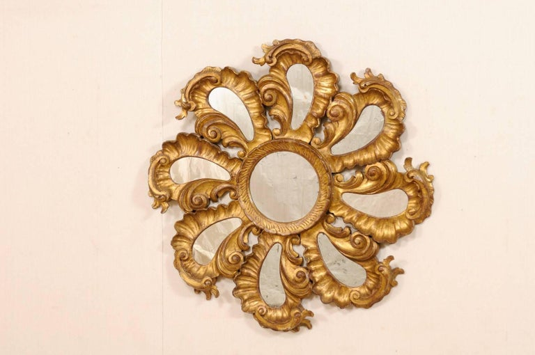 A vintage Italian good gilt and carved wood flower-shaped mirror. This spectacular gilded Italian mirror is comprised of circular-shaped center mirror which is surrounded by whirling, and richly carved petal-shaped extensions, each with mirrors at