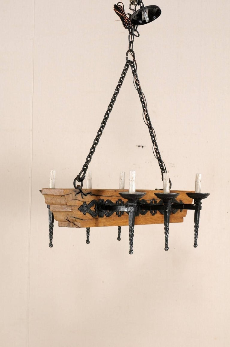 A French six-light wooden beam and iron arms chandelier from the mid-20th century. This vintage French chandelier has a central wooden beam with six torch-style iron arms, three at each opposing side. The six torch light arms with spiralized posts