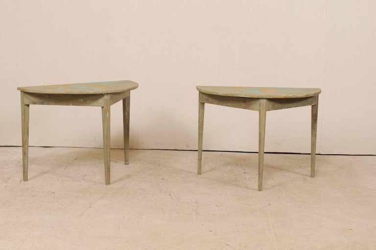 A pair of 19th century Swedish painted wood demilune tables. These antique Swedish demilune tables features a semi-circular top over a triangular shaped apron. Their tops have a custom painted half-star design in a turquoise and cantaloupe and the