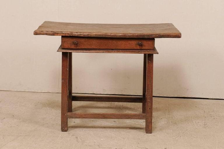 An 18th century Brazilian table. This antique Brazilian table has a single drawer and wooden stretchers along all sides, and an overhanging rectangular-shaped top. The table is comprised of peroba wood (a tropical native hardwood, 35% harder than