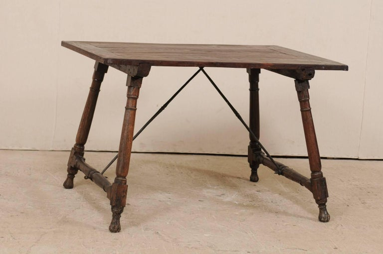 An antique Italian wood and iron stretchered desk table from the late 18th-early 19th century. This Italian desk features a rectangular-shaped top which is raised with outwardly tilting turned legs, which are supported with turned beams at each far