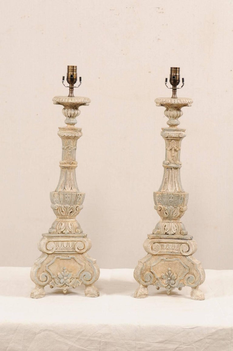 A pair of Italian style carved and painted table lamps. This pair of table lamps have been hand-carved and painted in the fashion of 18th and 19th century Italian candlesticks. They are decoratively carved in floral, leaf, and scroll motifs. Each of