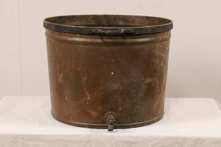 A vintage French large-sized copper kitchen pot. This mid-20th century French farmer's kitchen pot is nicely sized at 2 ft wide. The pot has two side handles and a spout (allows for easier drainage of liquids) which is located at the bottom